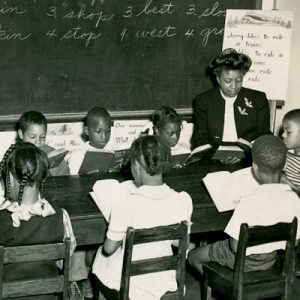 A segregated classroom with young, African American students learning from their teacher.